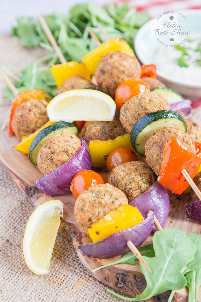 A close up of four falafel and Mediterranean vegetable kebabs.