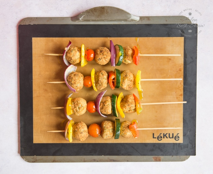 Four falafel And Mediterranean vegetable kebabs laid on a silicone mat on a baking tray, ready to be cooked.