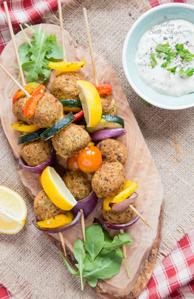 Top down view of four falafel And Mediterranean vegetable kebabs on an olivewood board. Next to the board is a shallow green bowl of tahini sauce.
