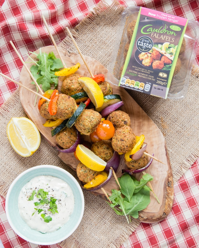 A top down view of four falafel And Mediterranean vegetable kebabs on an olivewood board. Next to the board is a shallow green bowl of tahini sauce and pack of falafels.