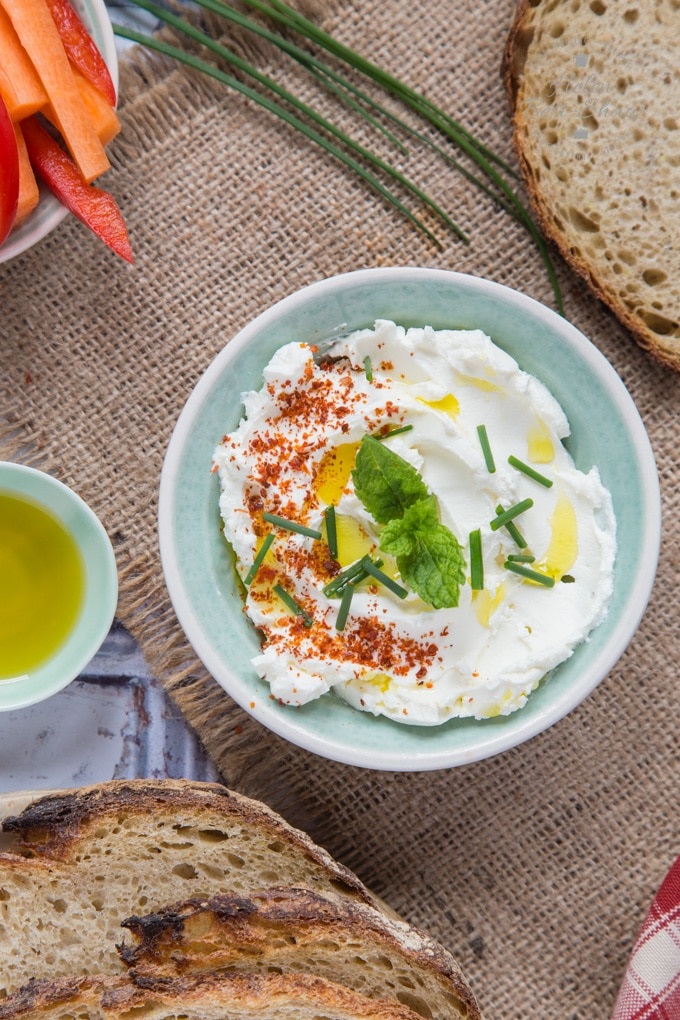 A top down shot of a pale green bowl of labneh, topped with chili flakes, chopped chives, mint and olive oil. Surrounding the bowl of labneh are slices of bread, some stalks of chives, a small dish of olive oil and some carrot sticks.