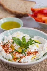 A shallow green bowl of fresh labneh, topped with a pinch of chili flakes, finely chopped chives, a sprig of mint and a slurp of olive oil. In the background are slices of bread, carrot stick and slice peppers in a bowl, and a small dish of olive oil.