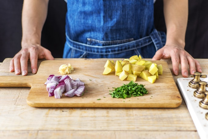 Ingridents for sag aloo on a wooden chopping board: diced potato, slice onions, crushed garlic and finely chopped coriander.