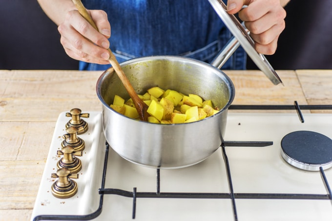 Cooking sag aloo: a saucepan of diced potatoes cooking in a curry sauce. The cook is removing the lid and stirring with a wooden spoon.
