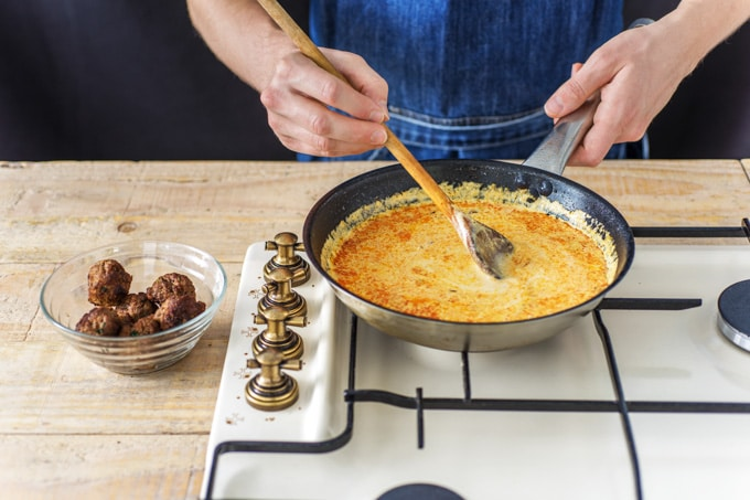 Cooking beef kofta curry: the cooks hands are show stirring a frying pan of creamy sauce. Alongside is a small glass dish holding the cooked beef koftas.