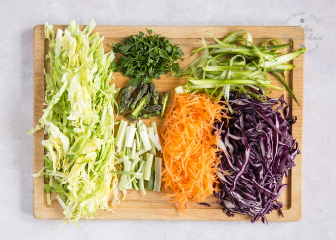 A wooden chopping board covered with prepared ingredients for asparagus salad: finely sliced hispi or sweetheart cabbage, asparagus, red cabbage, carrots, spring onions or scallions, and coriander.