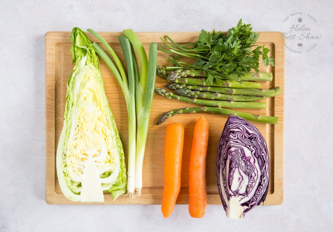 A rectangular wooden chopping board coved with the ingredients for asparagus salad: hispi or sweetheart cabbage, asparagus, red cabbage, carrots, spring onions or scallions, and coriander. Washed as necessary and ready to be finely sliced.
