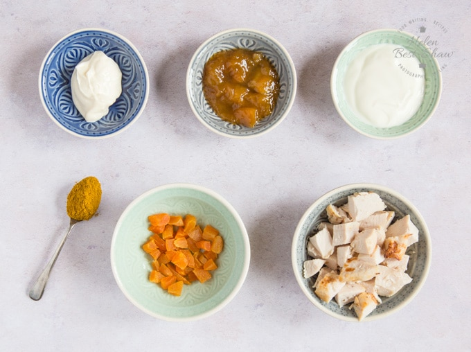 A mise en place of the ingredients for healthy coronation chicken. Mayonnaise, mango chutney, yogurt, cooked chicken and diced apricots are in separate bowls, arranged in two rows. Also seen is a teaspoon of curry powder.