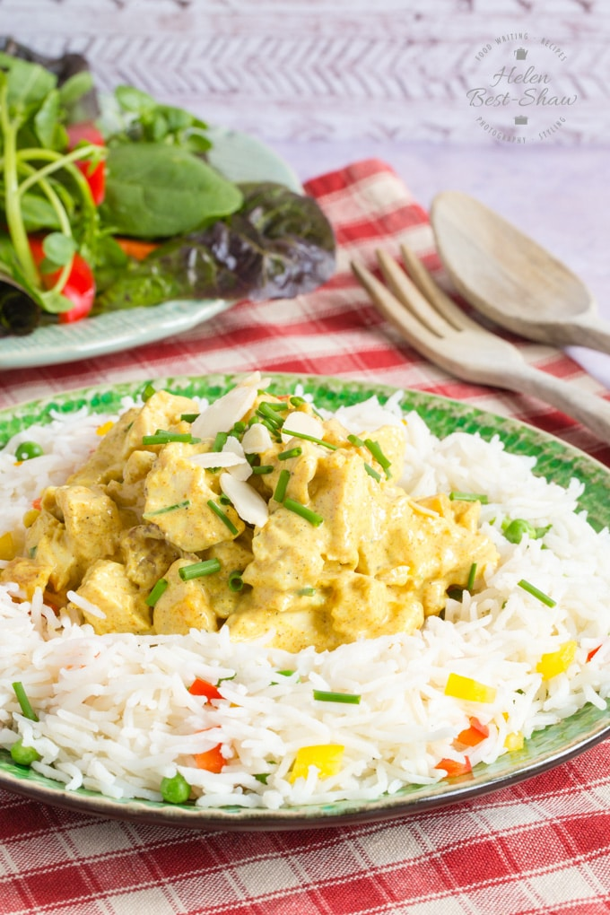 A plate of healthy coronation chicken on a rice salad; the chicken is garnished with slivered almonds and chives, and the rice salad contains diced yellow and red peppers and green peas.