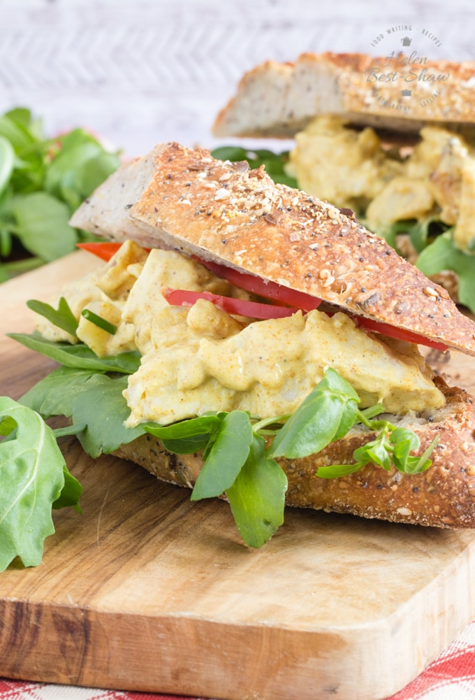 A coronation chicken sandwich with green salad leaves, made on a rustic brown baguette. It's on a wooden board, with another sandwich in the background.