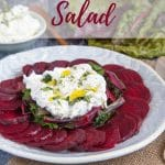 A plate of vibrant slices of beetroot arranges in a corcle around a pile of steamed greens topped with an organo tzatziki labneh text overlay reads Beet and labneh salad