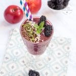 A glass goblet containing blackberrt and apple smoothie garnished with mixed seeds, mint and blackberries. In the glass there are two striped straws. In the background there are fresh blackberries and apples.