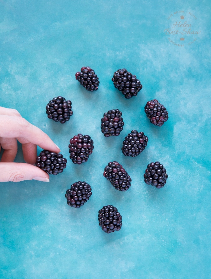 Large and juicy Driscolls sweet Victoria blackberries arranged on a blue background. A hand holds one of the fruit.