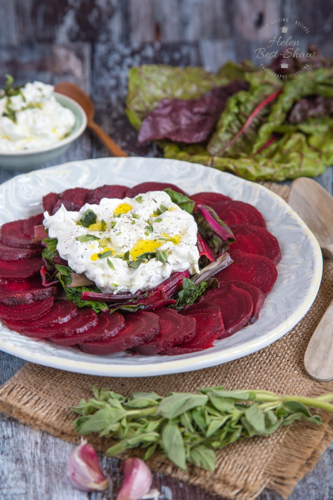 A plate of vibrant slices of beetroot arranges in a corcle around a pile of steamed greens topped with an organo tzatziki labneh