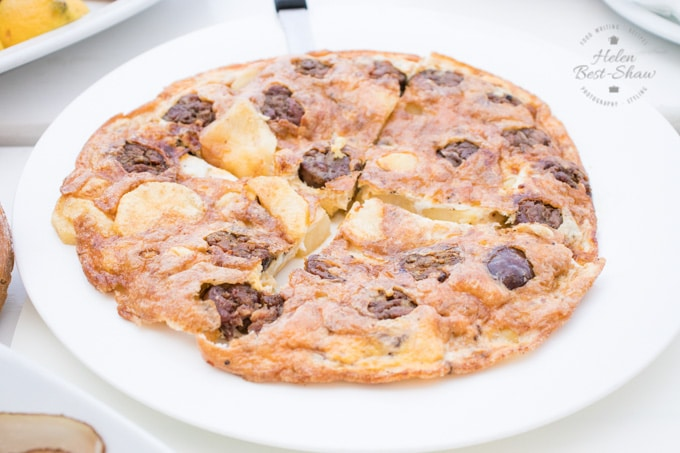 A tortilla made with sausage and potatoes on a white plate