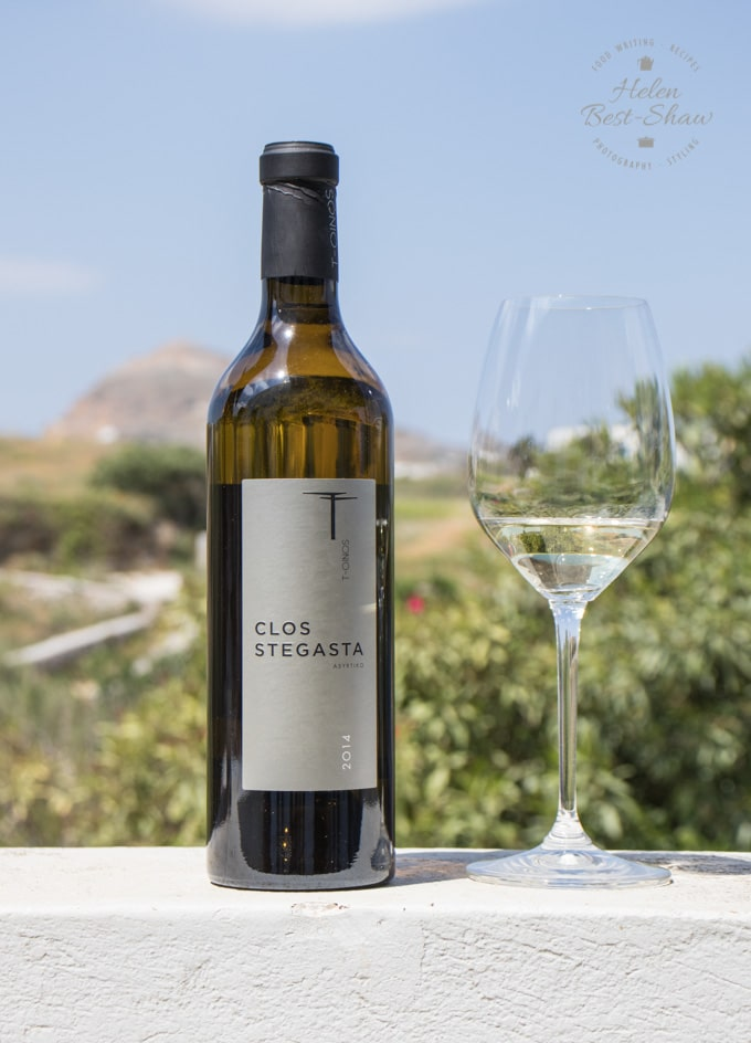 A bottle of Clos Stegasta wine, standing on a stone wall with vineyards behind
