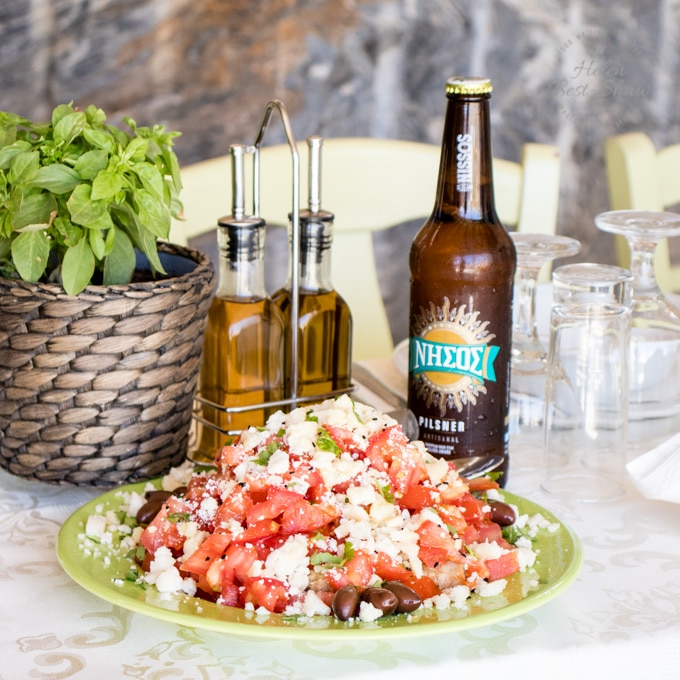 A table set wtih a plate of greek salad, bottle of beer, cruet and a pot of oregano.