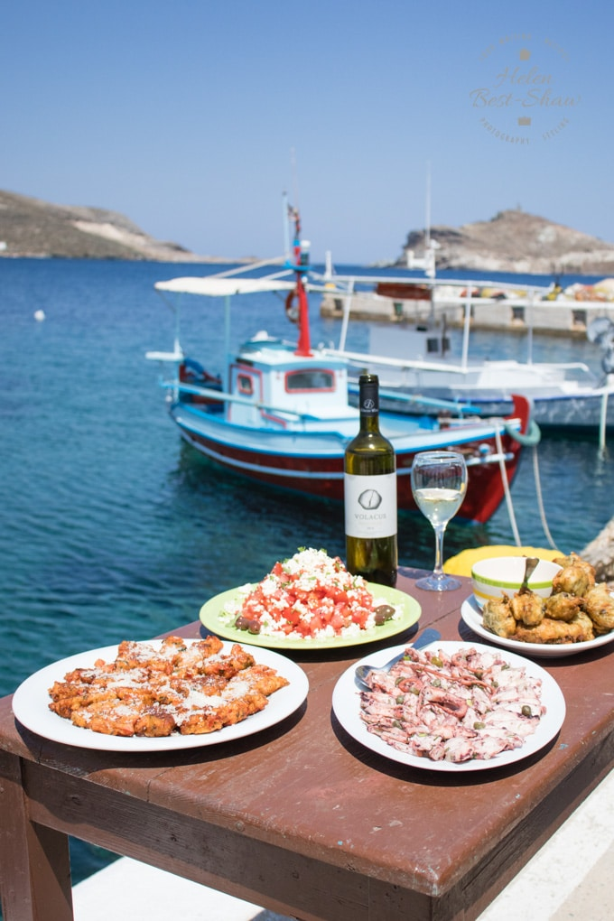 A table set is set with traditional dishes from the Greek Island of Tinos, in the background is the blue sea and a few fishing boats