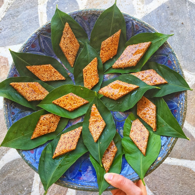 A plate of Pastli cut into diamonds and served on lemon leaves, arranged on a blue circular plate