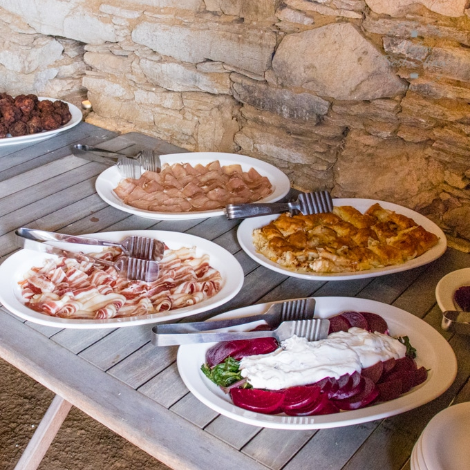 A wooden table standing against a stone wall with plates of Greek Charcuterie and a plate of beetroot and yogurt salad