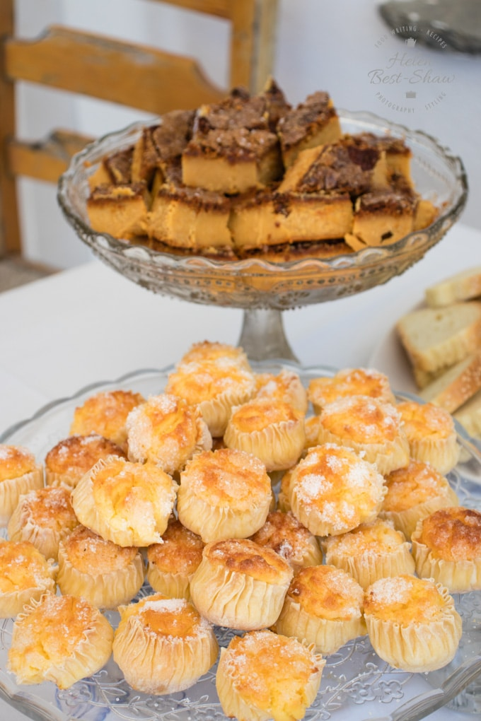 A two teir cake stand packed with bite sized pastries.