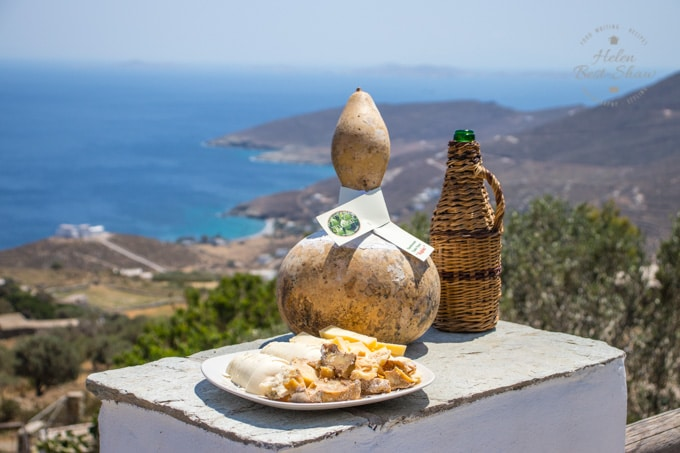A Tinios Kariki cheese made in a gourd. Standing on a table with a wicker covered bottle of rati