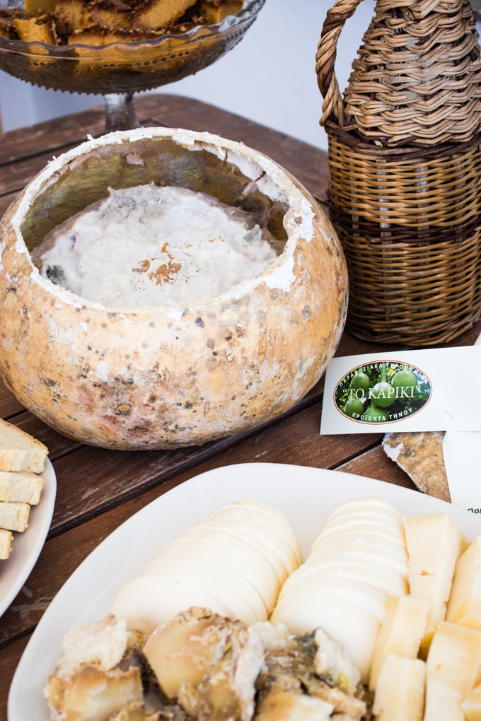 A table with a plate of a selection of Greek cheeses, and a opend gourd containing an aged kariki cheese