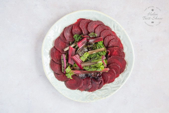 A plae of lightly steamed chard or beet greens surrounded by sliced beetroot viewed from above.
