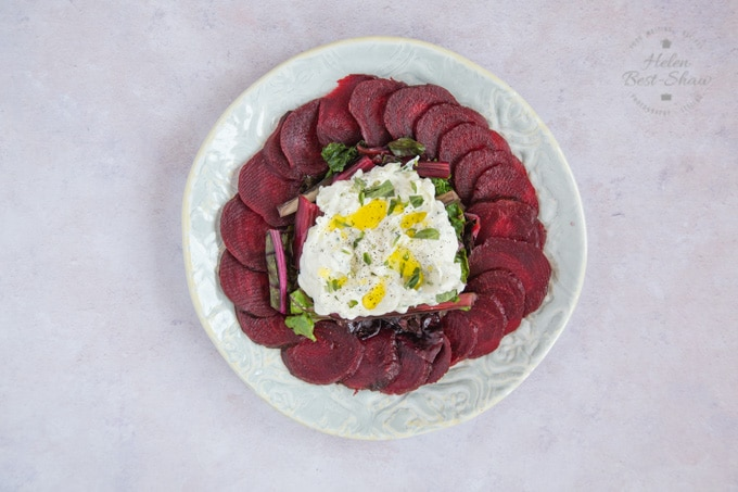 A plate of sliced beetroot and cooked chard topped with a tzatziki labneh