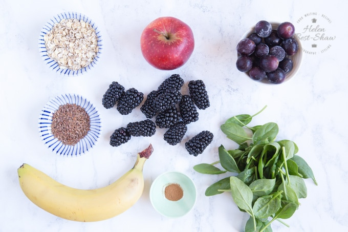 Ingredients for a blackberry and apple smoothie viewed from above arranged on a marble background the image shows a banana, pile of spinach. apple, blackberries and grapes. Also seen are bowls of oats, flax seeds and cinnamon