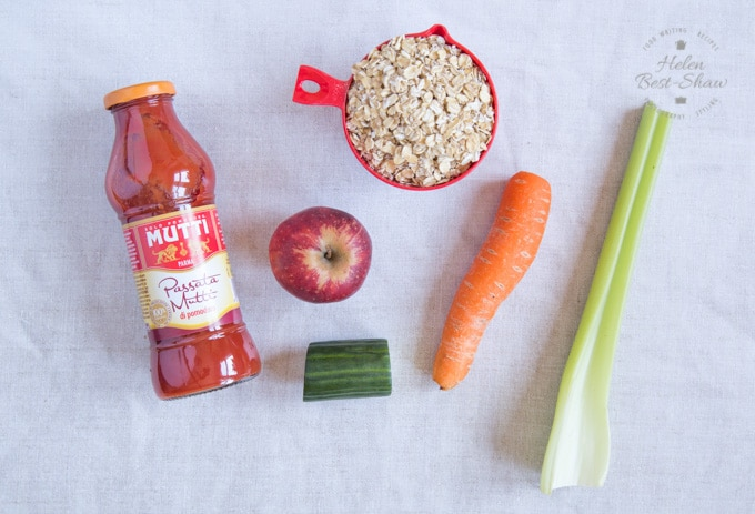 A top down shot of the ingredients of savoury tomato overnight oats: Mutti tomato passata, an apple, cucumber, carrot, celery and jumbo rolled oats.
