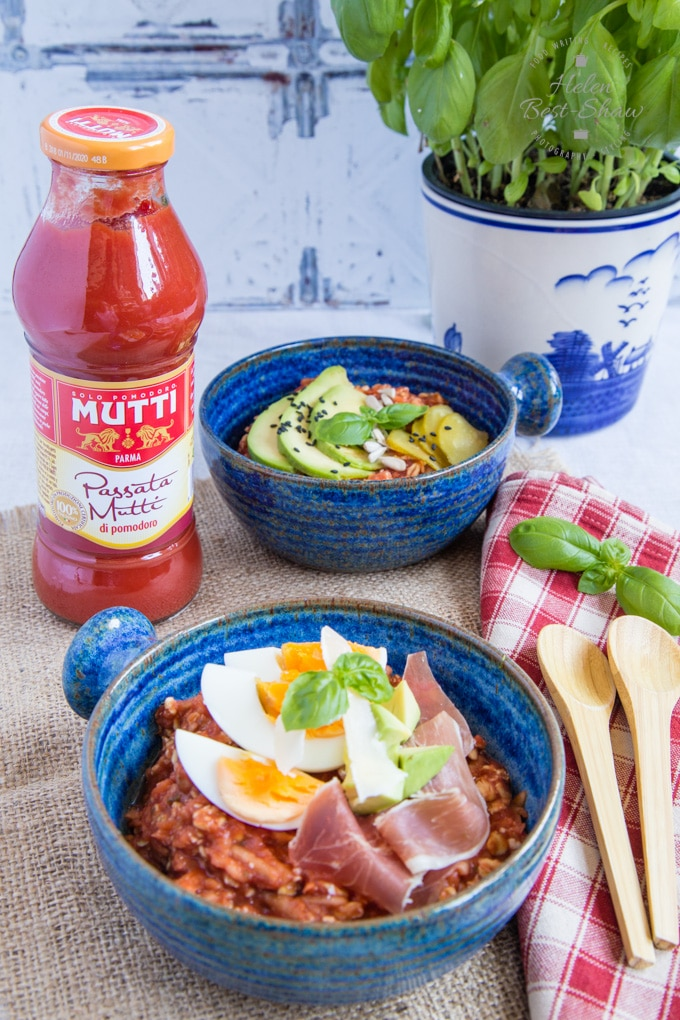 Two bowls of savoury tomato overnight oats in blue bowls. One topped with sliced avocados and pickled cucumbers, the other with parma ham slices and a quartered boiled egg. Alongside the bowls is a bottle of Mutti tomato passata.