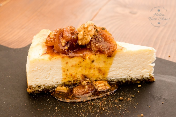 A slice of cheesecake presented on a black board topped with figs, walnuts and orange in a thick sticky sauce.