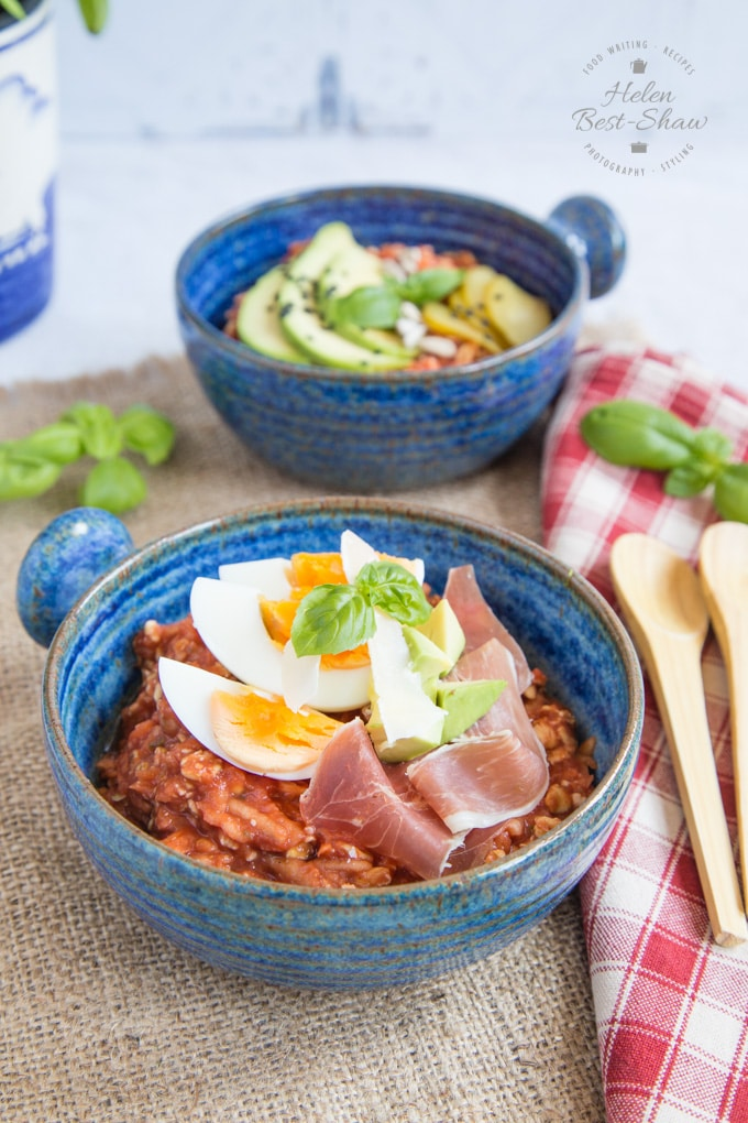 Two bowls of savoury tomato overnight oats. In the foreground, the dish is topped with a quartered boiled egg and slices of air-dried ham. The bowl in the background is topped with sliced avocado and pickled cucumber.