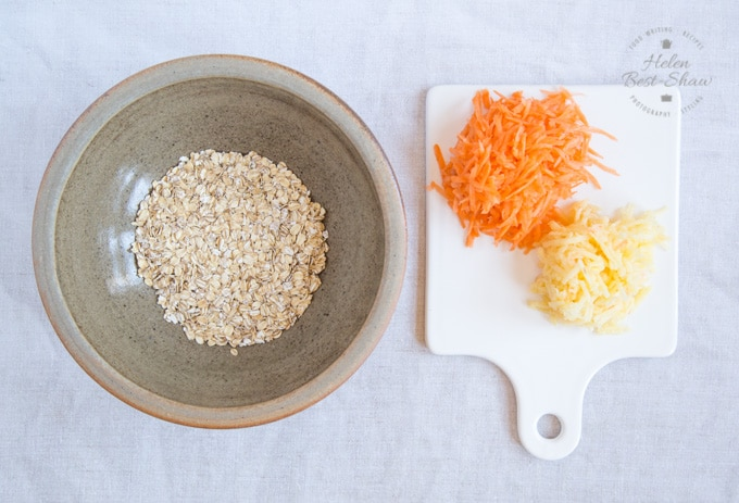 A top down view of a brown pottery bowl containing rolled jumbo oats next grated carrot and apple on a white porcelain square.