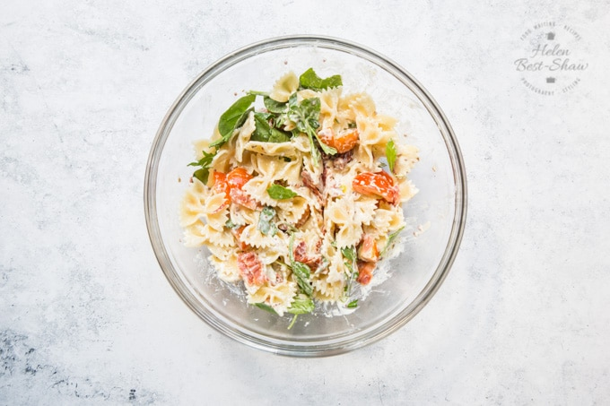 BLT pasta salad, top down view. Ingredients mixed in a glass bowl.