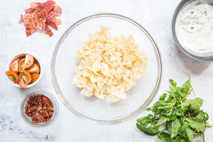 BLT Pasta salad. Cooked pasta in a glass bowl. surrounded by dressing, tomatoes, and basil.