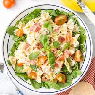 BLT pasta salad from above, on a green salad and garnished with basil.