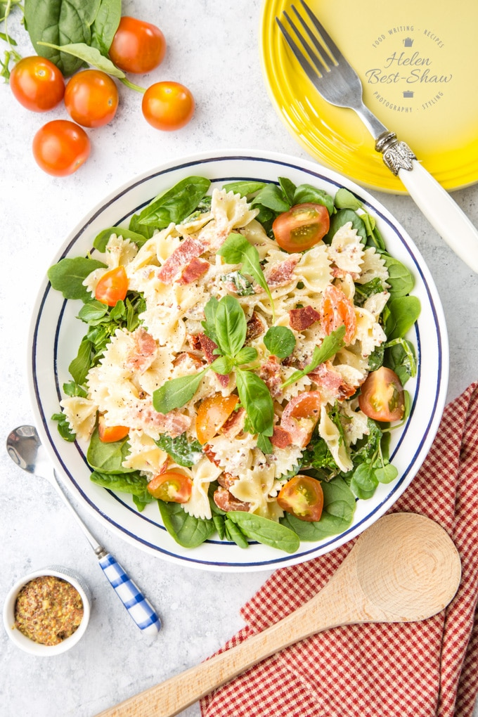 BLT pasta salad from above, in a white and blue bowl. Surrounding the salad are cherry tomatoes, basil leaves, a yellow plate and fork, and a wooden spoon and gingham cloth.
