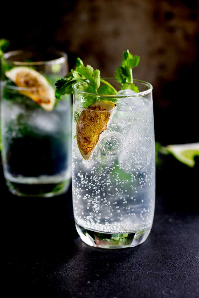 A highball glass full of fizzy gin and tonic, garnished with a charred slice of lime and a sprig of coriander, against a black background. Out of focus at the rear is another full highball glass, similarly garnished.