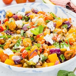 A close up of mixed grain roast vegetable salad in a white and blue patterened plate.