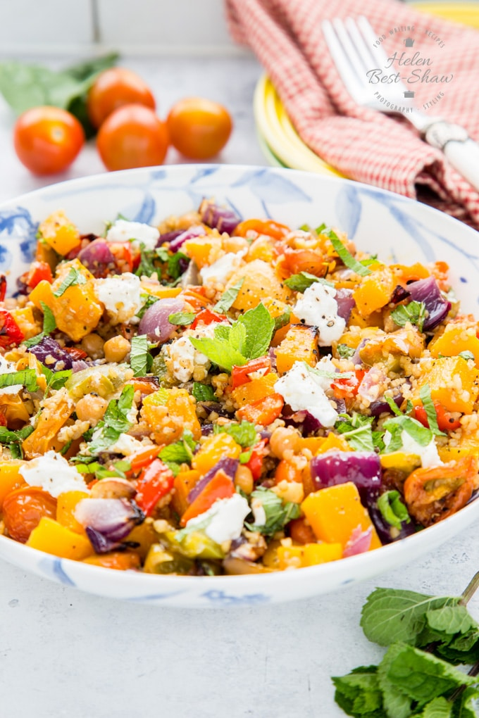 A mixed grain roast vegetable salad on a blue and white bowl. In the background are basil and cherry tomatoes and a fork on a gingham cloth.