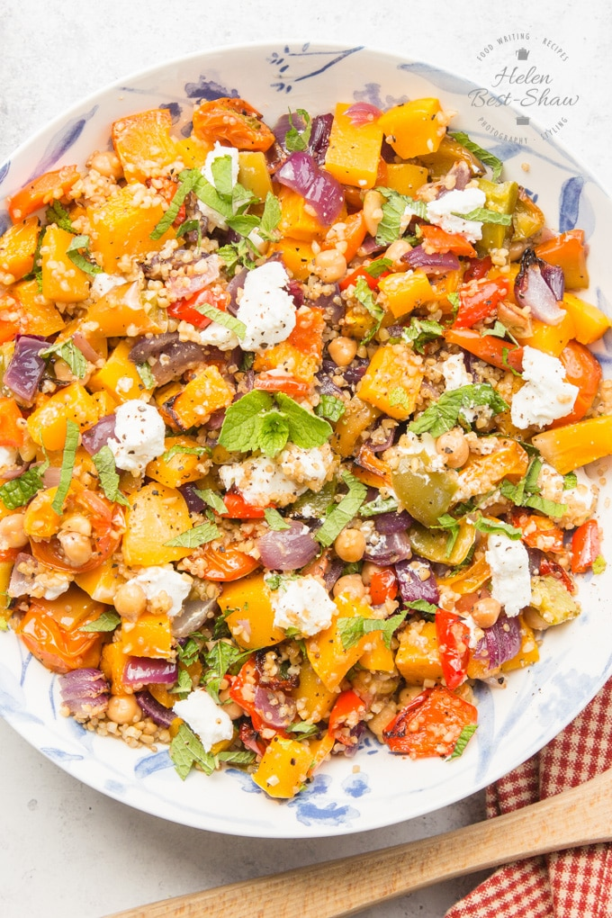 a top down shot of a bowl of mixed grains and roasted vegetable salad with goats cheese