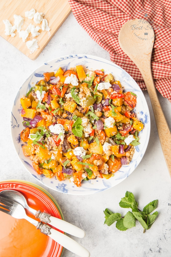 A top down shot of a mixed grain roast vegetable salad in a blue and white patterened plate. Surrounding the plate are a wooden spoon on a gingham cloth, a chopping board with crumbled goats cheese and an orange plate with spoon and fork.