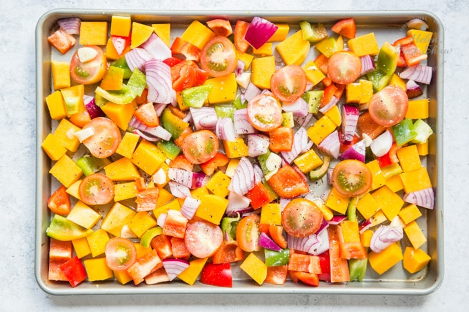 Mixed grain roast vegetable salad - vegetables ready for roasting spread out in a roasting tin.
