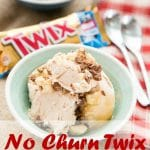 Three scoops of no churn twix ice cream in a shallow green bowl. A bar of Twix chocolate in the background, along with another bowl of ice cream. Two spoons on a red and white checked cloth are on the right of the picture.