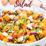 A mixed grain roast vegetable salad on a blue and white bowl. In the background are basil and cherry tomatoes and a fork on a gingham cloth. - text overlay reads roast veggie salad