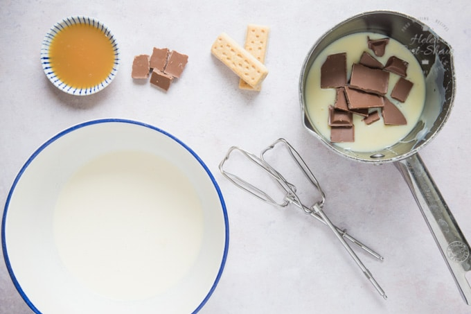 A top down view of the ingredients for easy no-churn Twix ice cream: a bowl of cream, ready for whipping. A small bowl of caramel sauce, some squares of chocolate and two shortbread fingers. A saucepan containing squares of milk chocolate and condensed milk.