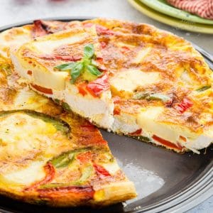 A close up of leftover roast chicken frittata, with a slice cut out and placed on top.