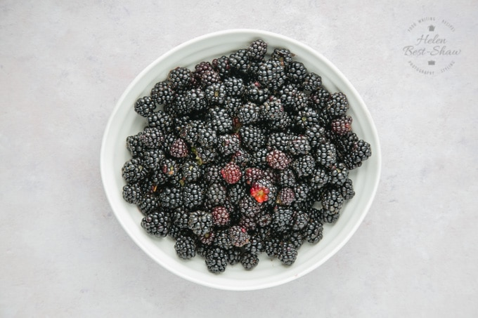 A large white bowl of blackberries on a mottled grey work surface, taken from above.